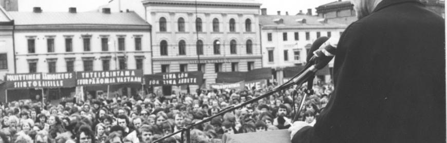 Svartvit bild tagen bakifrån på C.-H. Hermansson, Vänsterpartiets dåvarande ordförande, håller tal på första maj någon gång på 70-talet. I bakgrunden syns den stora åhörarskaran.