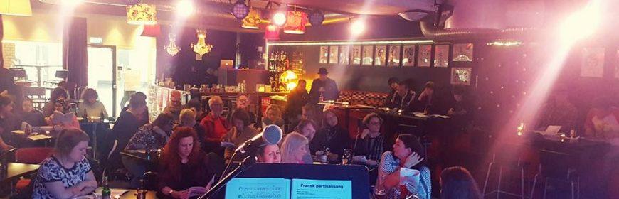 Bild tagen från scenen på ett rum fullt med människor som sitter ner och sjunger text från ett pappar som de håller i händerna.