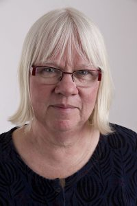 Porträttfoto på Eva Olofsson, kommunalråd för Vänsterpartiet i Västra Götalandsregionen. Hon har en svart tröja och glasögon med röda bågar. Hon tittar in i kameran men ett litet leende.