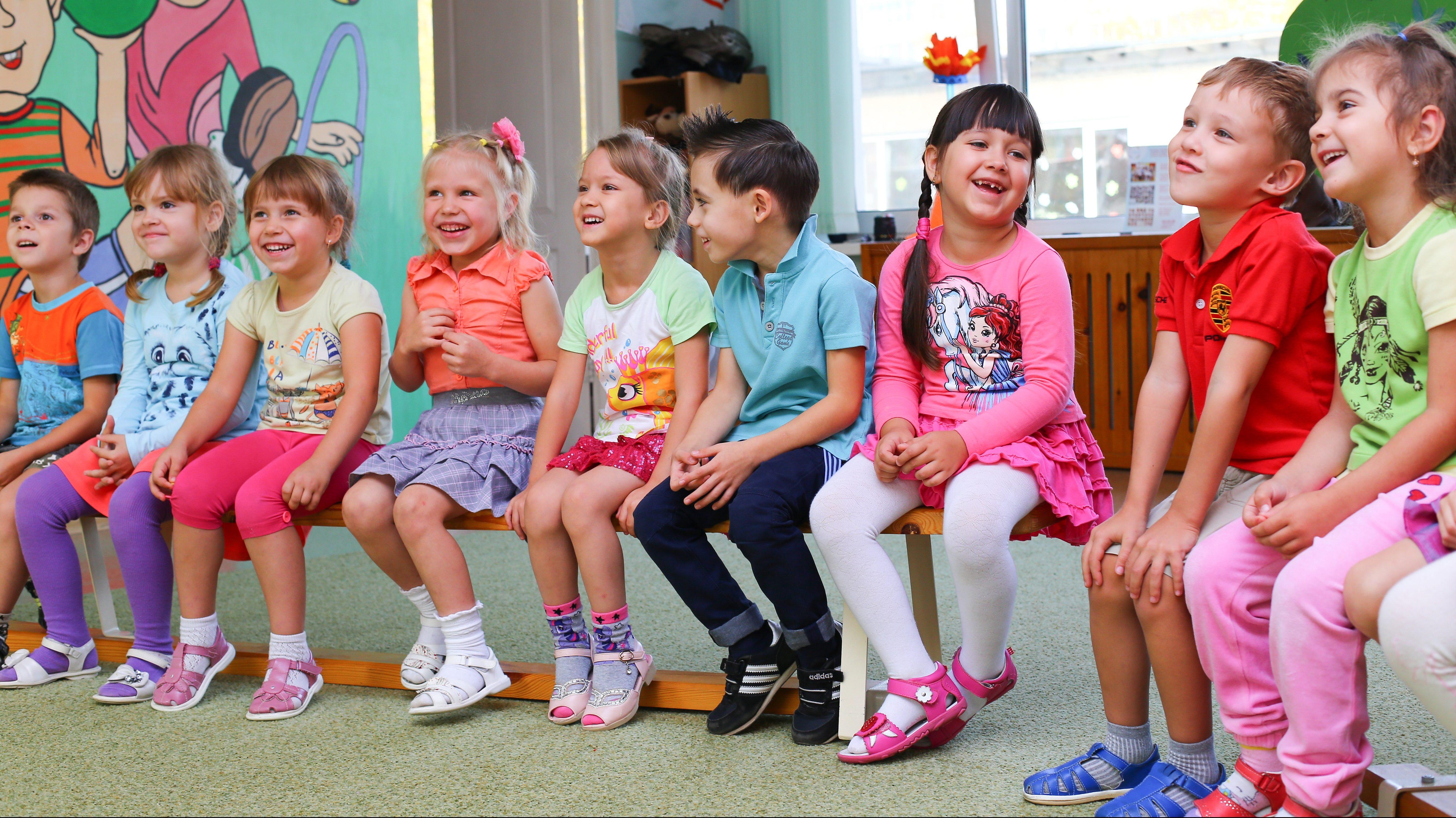 Tio leende barn i färgglada kläder sitter på en bänk i en halvcirkel. Bakom barnen syns ett fönster och en öppen dörr syns till vänster. Väggen på vänster sida är målad i ljust grön färg med två lekande barn. Golvet är klätt med ljusgrön heltäckningsmatta.