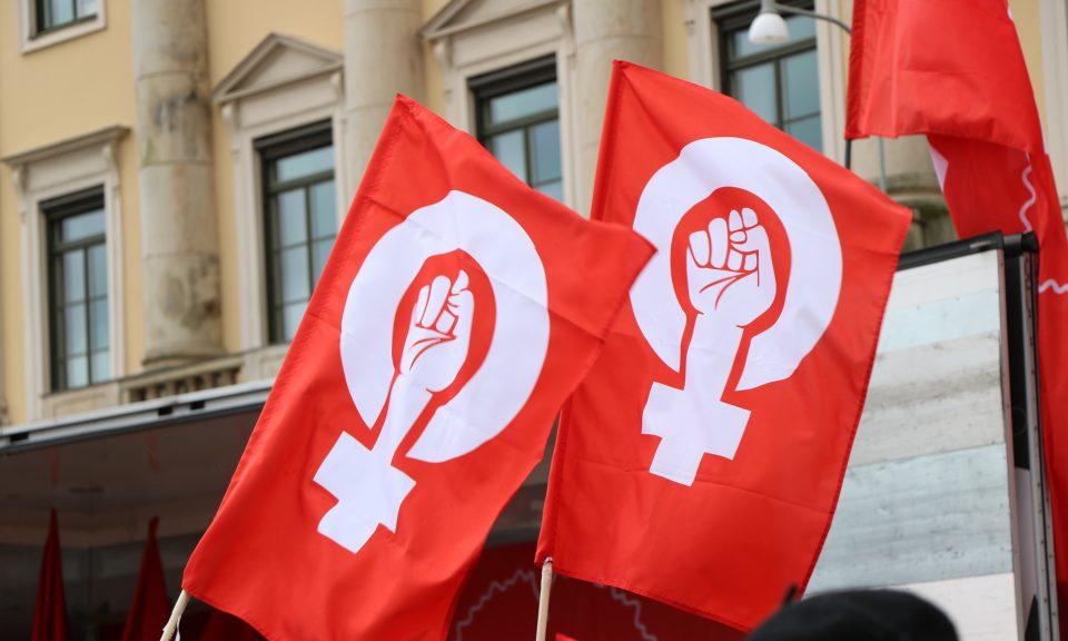 två röda flaggor med knuten näve i en kvinnosymbol. I bakgrunden syns Göteborgs stadshus.