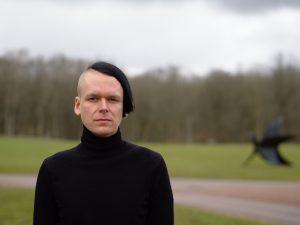 John Edström fotad framifrån. Gräsmatta utanför fokus i bakgrunden.