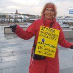 """Gertrud Ingelman med skylt på magen med texten """"Stoppa Skeppsbrogaraget"""""""