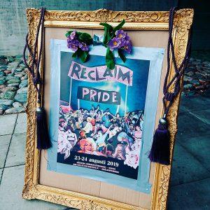 Affisch för Reclaim Pride i guldram med gardintofsar hängande på sidorna.