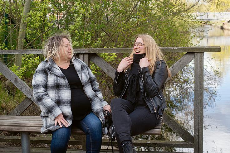 Bild på Emma och Maria på en parkbänk skrattandes.