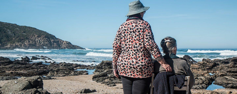 TVå älder kvinnor blickar ut över havet. De har ryggen mot betraktaren. En sitter i en solstol.