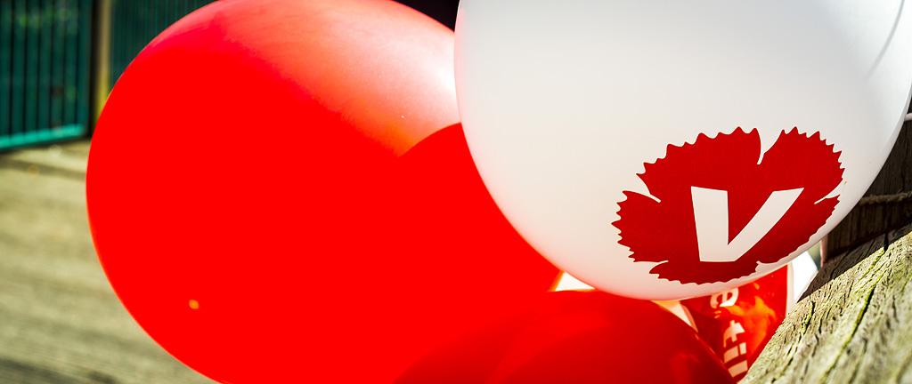närbild av ballonger. En ballong har Vänsterpartiets logga tryckt på.