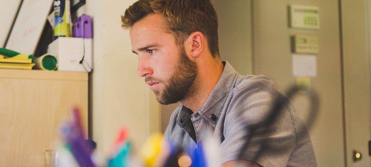 man arbetar vid skrivbord. Suddiga pennor i förgrunden.