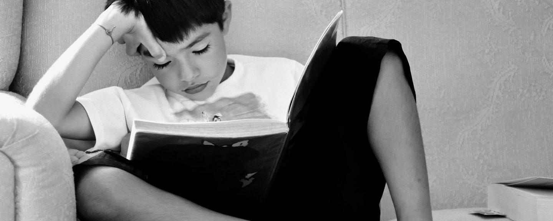 Pojk sitter i soffa och läser en bok