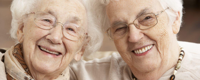 Två äldre kvinnor som ler