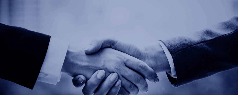 två personer i kostym skakar hand