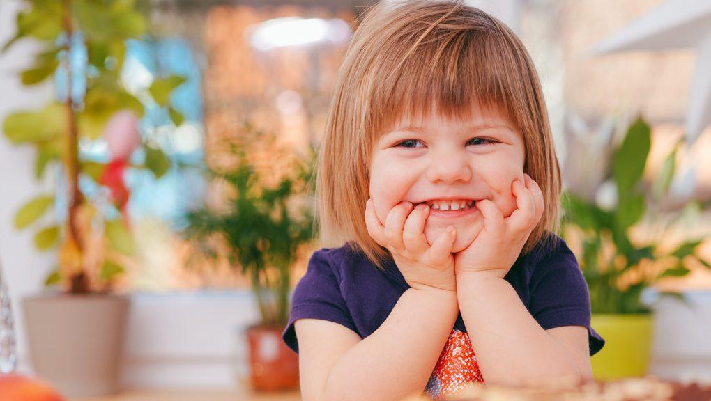 barn som är glad sittandes vid matbord