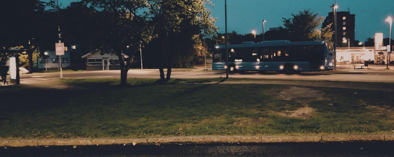 Blå buss kör förbi gräsyta på kvällen