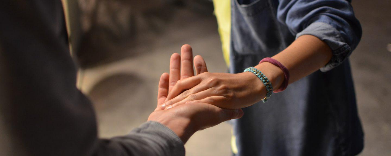 en person som lägger sin hand i en annan persons hand