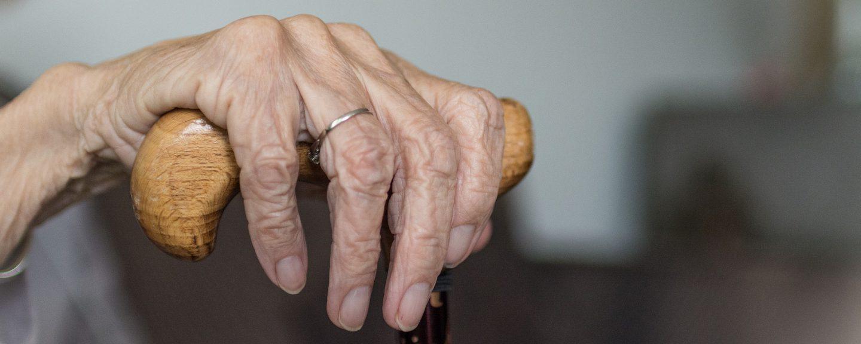 mycket gammal kvinnas hand som håller i en käpp