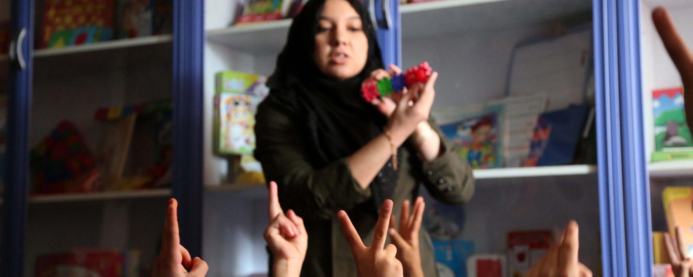 Förskollärare visar upp pusselbitar för barn