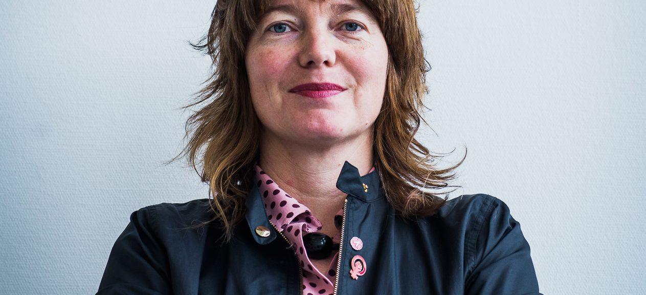 Porträttbild på Malin Björk. Hon står med armarna i kors och tittar in i kameran.