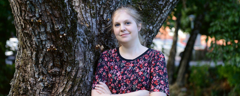Karin Karlsson med armarna i kors lutad mot ett träd