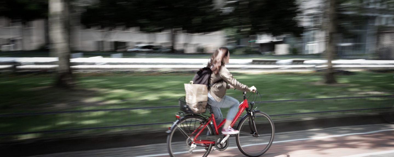 Kvinna cyklar på röd cykel i stadsmiljö