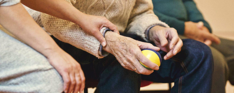 Kvinna tar pulsen på äldre man som håller boll.