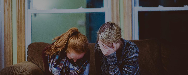 Två ledsna kvinnor sitter i en soffa. Kanske gråter de.